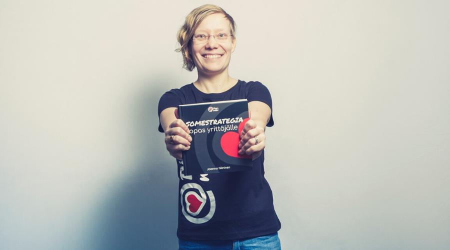 Sollertiksen toimitusjohtaja Joanna Niininen pitelee kirjoittamaansa Somestrategia - Opas yrittäjälle kirjaa.