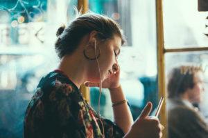 Nainen katsoo kännykkää kuulokkeet korvilla