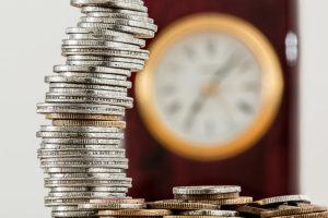 Mittaa menestystäsi, jotta tiedät missä olet menossa. Kuvassa rahoja sekä kello.